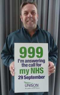 Joe, a paramedic, holds up a promotional poster for the Save Our NHS demon on 29th September 2013