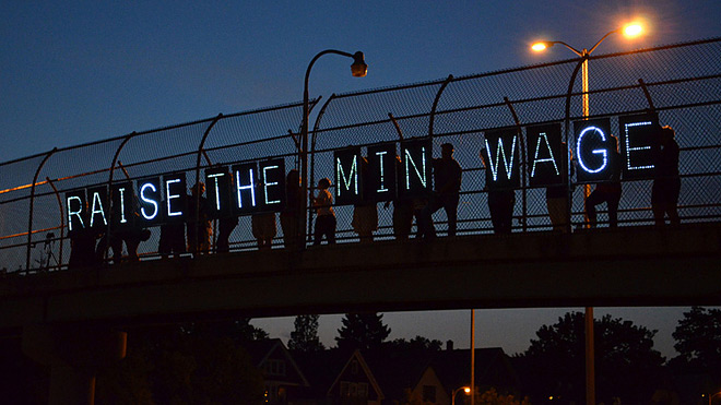 Raise the minimum wage lighted signs on overpass