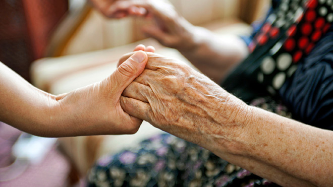 Photo: close-up of an elderly person's hands being held by a much younger person's hands (to suggest elderly care work).