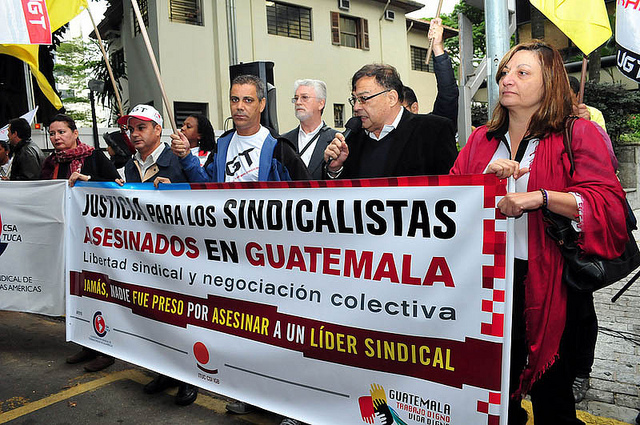 Marching trade unionists in Brazil hold a banner calling for justice for trade unionists murdered in Guatemala