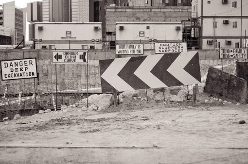 """Picture of warning signs on Qatar building site including """"danger blind curve"""" and """"caution slippery surfaces"""""""