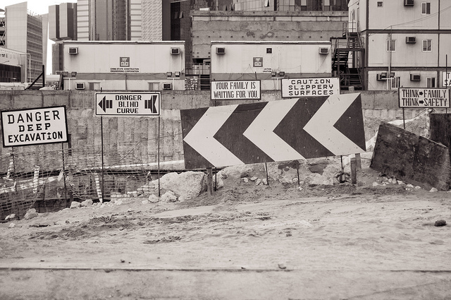 "Picture of warning signs on Qatar building site including ""danger blind curve"" and ""caution slippery surfaces"""