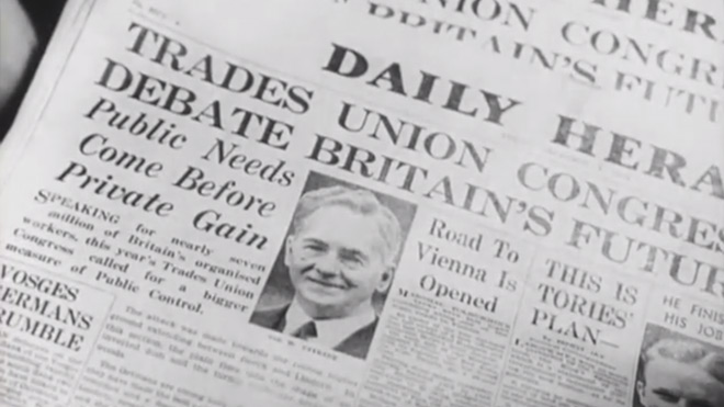 Film still of newspapers in print works, with story about unions
