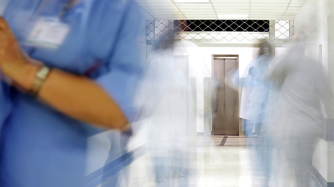 Image of a hospital corridor with NHS staff walking through it.