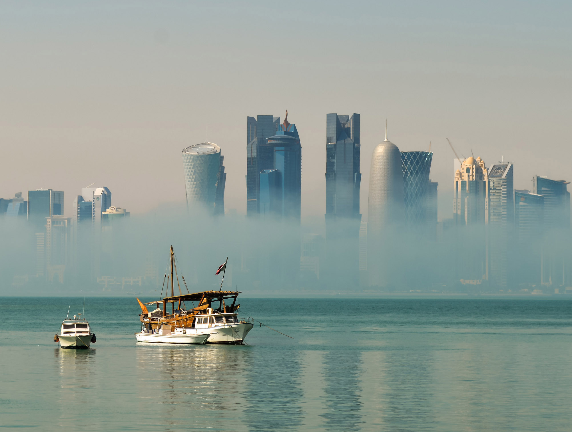 A picture of Doha from the water, with skyscrapers rising above from dawn mists