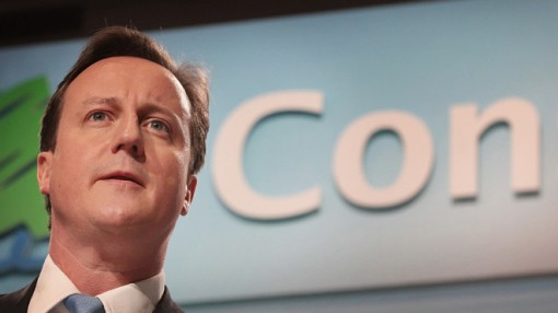 "David Cameron beneath the letters ""Con"" from ""Conservatives"""