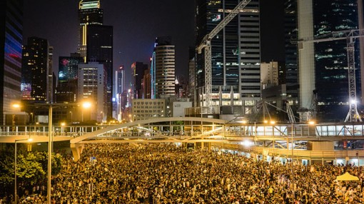 Many thousands of protesters cram into Beijing's streets beneath a modern skyline, lit yellow and orange by street lamps.