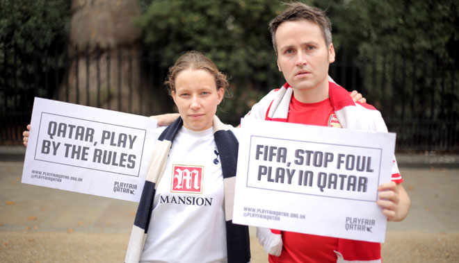 A Tottenham fan and an Arsenal fan stand side by side holding protest signs