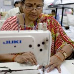 Photo of a female garment factory worker using a sewing machine in a factory in New Delhi.