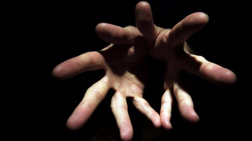 A pair of hands emerge from shadow, fingers first, implying a magic trick