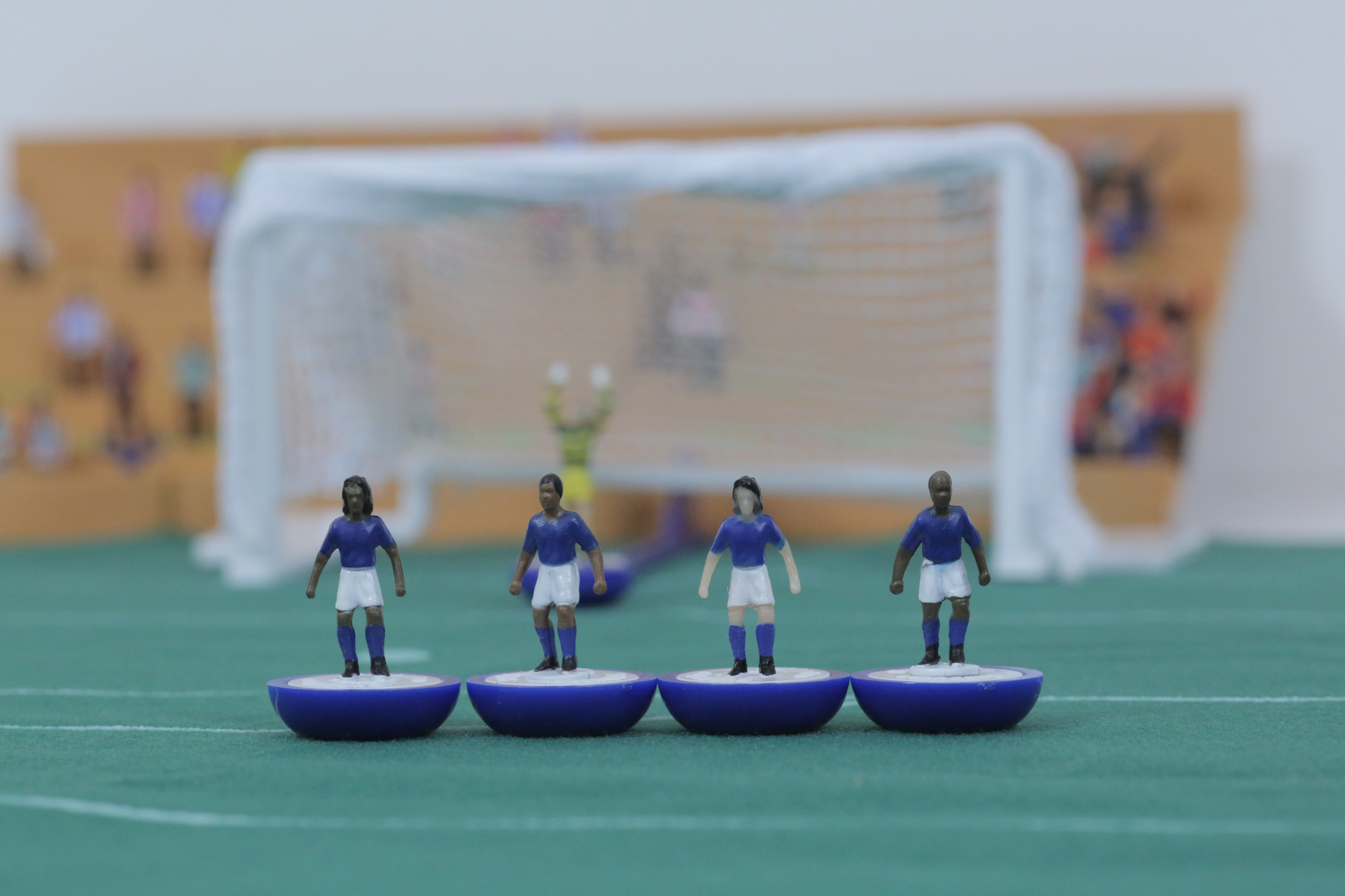 Toy football figures line up to protect their goal.