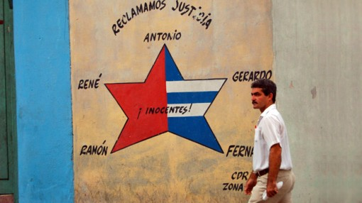 A man walks past a wall in Cuba decortaed with a star-shaped mural commemorating the members of the 'Cuban 5'