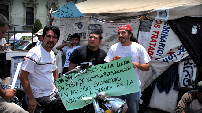 Guatemalan protestors hold up a sign in Spanish
