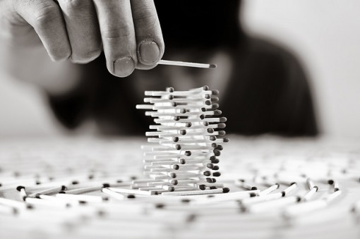A man patiently builds a delicate match-stick structure