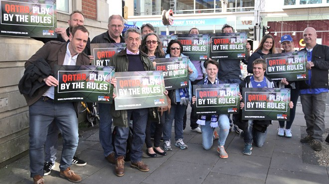 """Chelsea fans holding """"Playfair Qatar"""" signs gather in front of Fulham Broadway tube"""