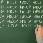 Teacher writing 'help' on blackboard