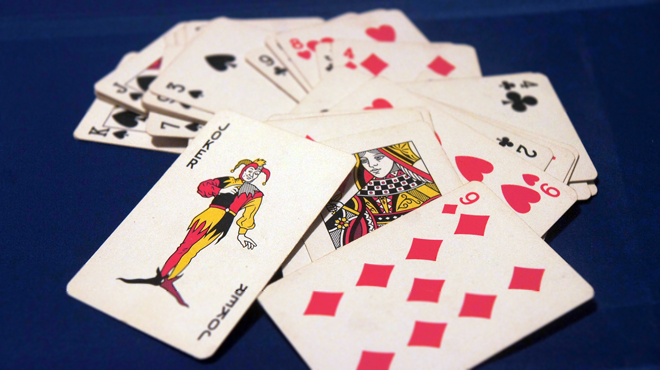 A pack of cards displays a joker and queen
