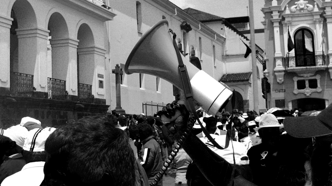 Quito, Ecuador - November 20, 2008: Protesters with megaphone outside Presidential Place in Quito. The demonstration was against Government cuts by the Union of Teachers and Lecturers of the Quito University.